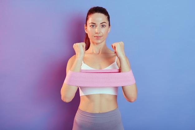 特別な抵抗の輪ゴムで白いトップトレーニング筋肉を身に着けている若い強い集中した女性は、運動し、手の運動をしています。