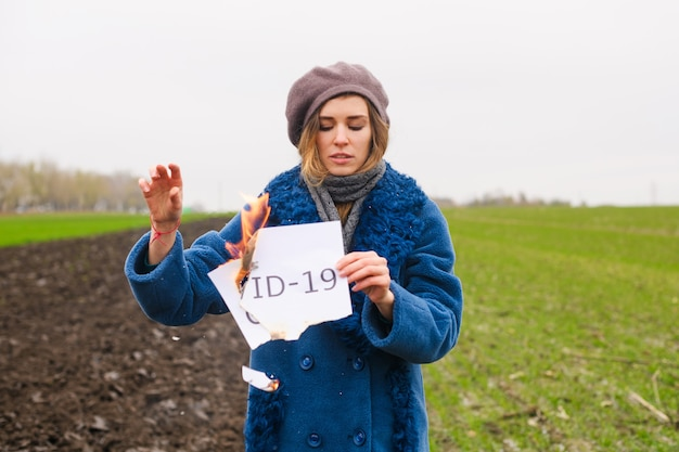 Молодая сильная отчаянная женщина в синем пальто и берете держит горящую бумагу с напечатанным словом covid-19 в изолированном месте