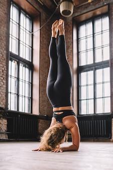 若い強い女性はロフトスタイルのクラスでヨガのアーサナを伸ばす複合体をします。シールシャーサナの位置。逆立ち。
