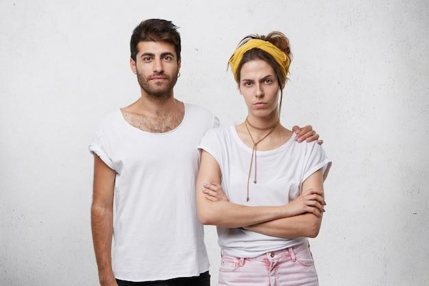 Молодой сильный мужчина с бородой и модной прической обнимает свою девушку, стоя у белой стены.