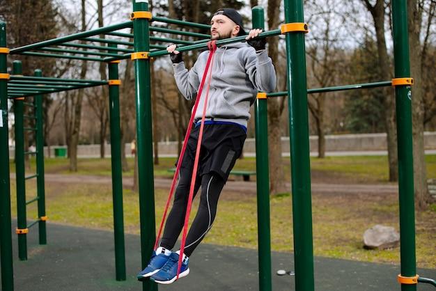 젊은 강한 남자는 도시의 여름에 운동장의 수평 막대에 턱걸이를합니다.
