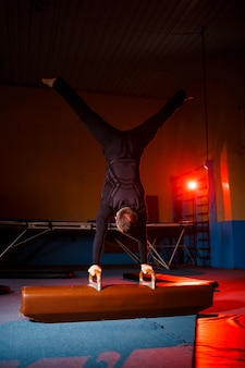 Молодой сильный человек делает упражнения стойки на руках. гимнастка занимается спортом в тренажерном зале