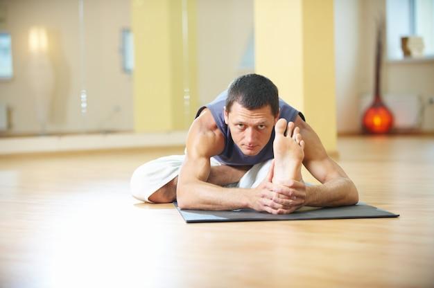 A young strong man doing yoga exercises. ardha padma paschimottanasana seated forward half lotus bend