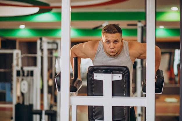 Молодой сильный человек, тренирующийся в тренажерном зале