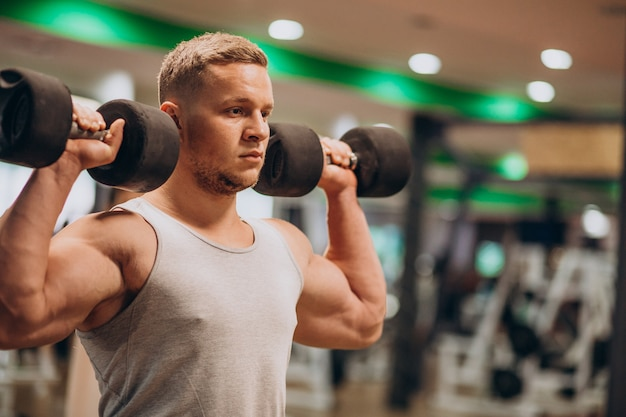 Giovane uomo forte che si esercita in palestra
