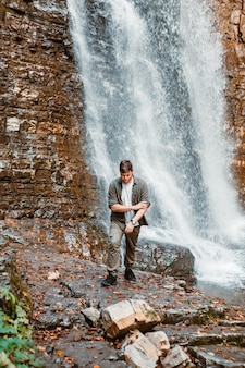 Young strong man hiker looking the waterfall copy space