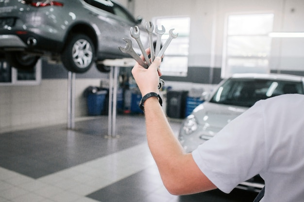 Young and strong man holds set of wrenches in hand. he shows it on camera. man shows it on camera. he stands in front of cars.