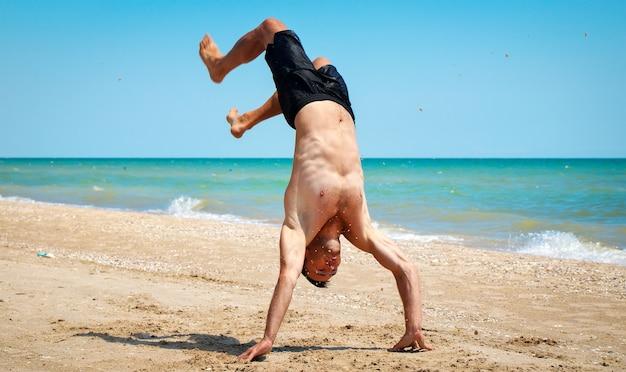 Молодой сильный мужчина в отличной физической форме стоит на руках на пляже у моря