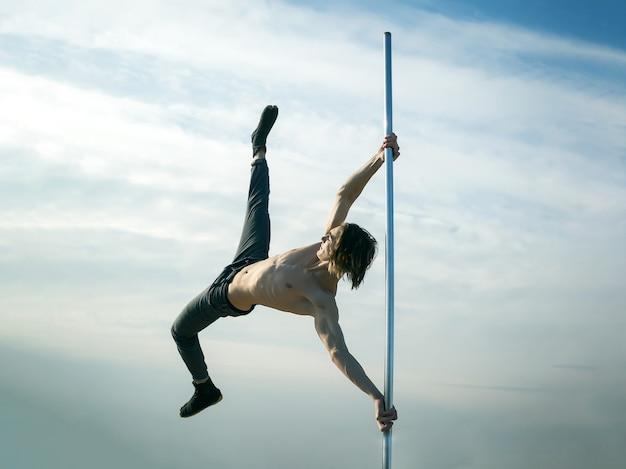 푸른 하늘 표면에 젊은 남자 댄서의 젊은 강한 남자 폴 댄스 폴 댄스 스포츠 폴 댄스 훈련