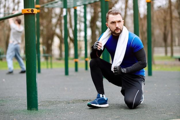 Молодой сильный мужчина отдыхает после тренировки на спортивной площадке летом в городе