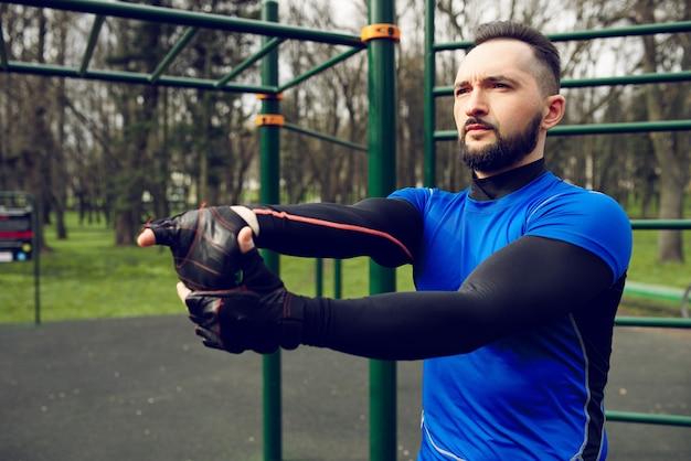 강한 젊은이 훈련 전에 그의 근육을 뻗어