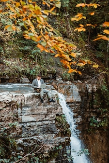 Young strong man working on laptop sitting at the edge of waterfall freelance hiking concept
