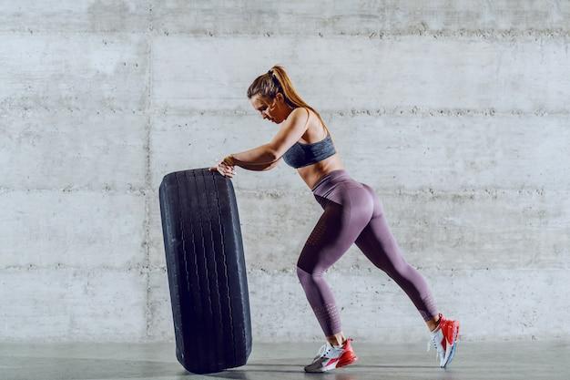 Молодая сильная мускулистая кавказская спортсменка в спортивной одежде с шиной переворачивания хвоста. концепция здорового образа жизни.