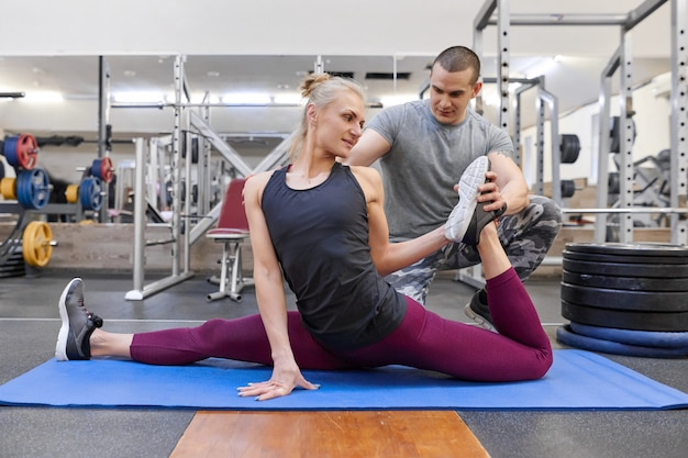 Young strong muscular man helping young athletic woman stretching