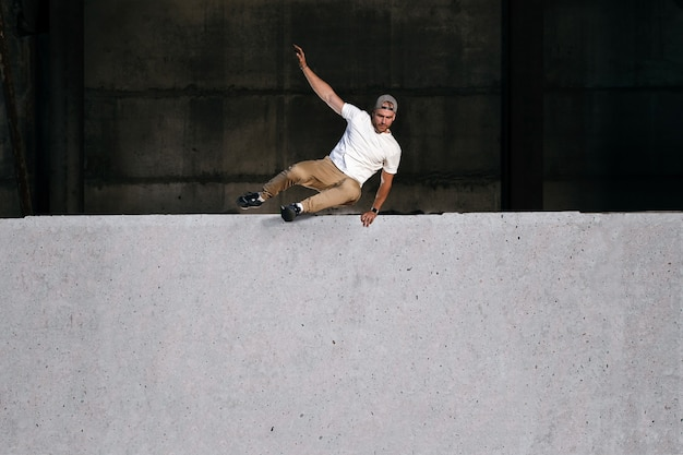 Young strong parkour and free running athlete jumping over the wall in urban environment