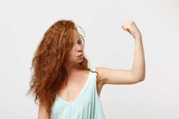 Young strong redhead woman girl in casual light clothes posing isolated on white background, studio portrait. people sincere emotions lifestyle concept. mock up copy space. showing biceps, muscles.