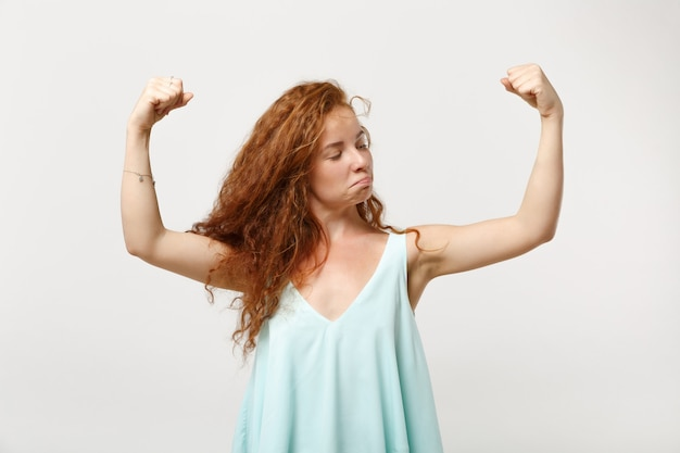 白い背景、スタジオの肖像画に分離されたポーズでカジュアルな明るい服を着た若い強い赤毛の女性の女の子。人々の誠実な感情のライフスタイルの概念。コピースペースをモックアップします。上腕二頭筋、筋肉を示しています。