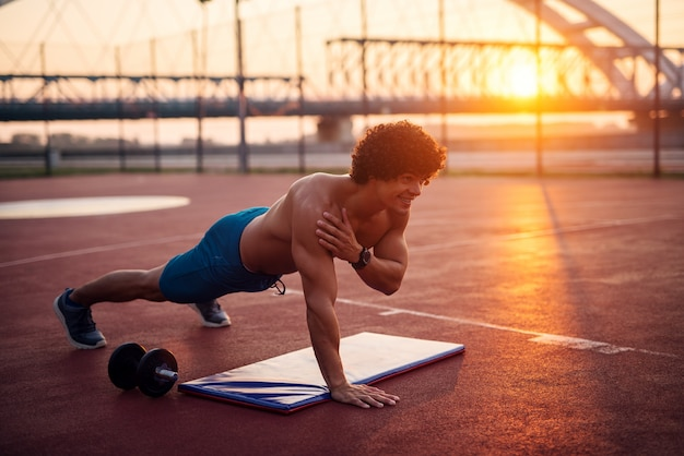 Young strong shirtless man doing plank exercises on a training field early in the morning.