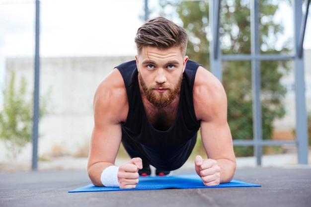Молодой сильный спортсмен делает планку на синем фитнес-коврике во время тренировки на открытом воздухе