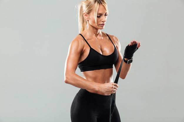 Молодая сильная спортсменка в боксерских повязках