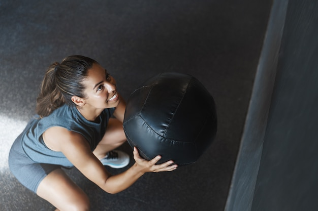 Young strong woman lifts ball up as perform squats exercise
