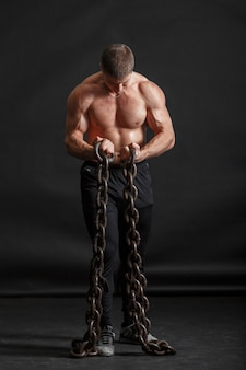 A young strongman is standing with two iron chains holding in his hands