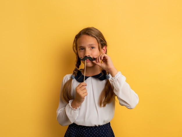 Young student acts like a senior teacher. yellow studio background