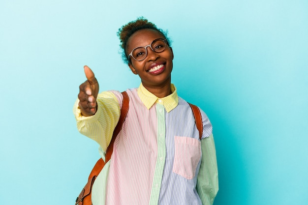 Young student african american woman over isolated background stretching hand at camera in greeting gesture.
