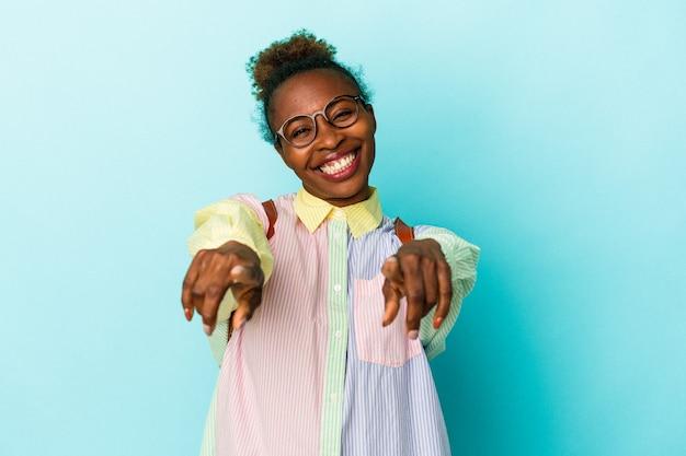 孤立した背景の上の若い学生アフリカ系アメリカ人女性は、正面を指している陽気な笑顔。