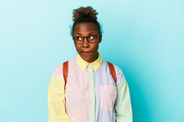 孤立した背景上の若い学生アフリカ系アメリカ人女性は混乱し、疑わしく、不安を感じています。