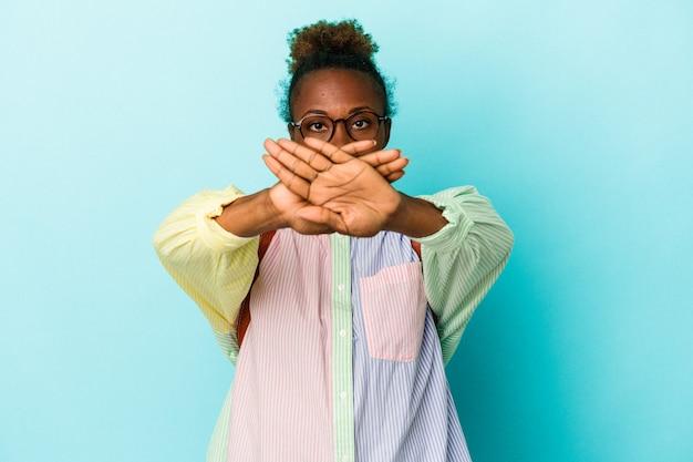 否定的なジェスチャーをしている孤立した背景上の若い学生アフリカ系アメリカ人女性