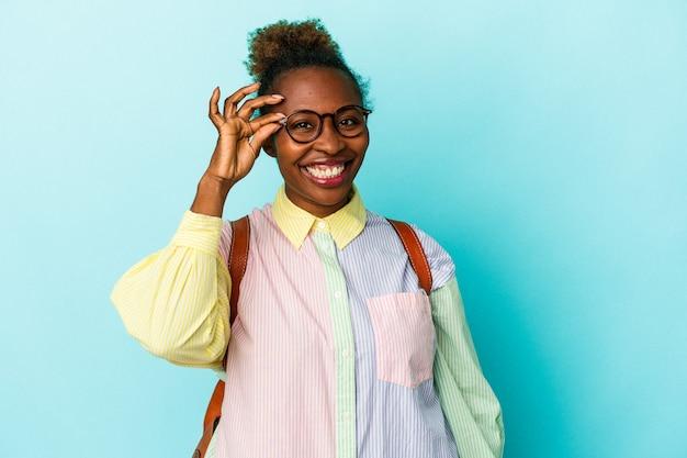 孤立した背景の上の若い学生のアフリカ系アメリカ人の女性は、目に大丈夫なジェスチャーを維持することに興奮しました。