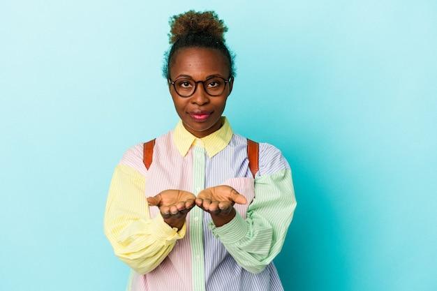 カメラに提供し、手のひらで何かを保持している孤立した背景上の若い学生アフリカ系アメリカ人女性。