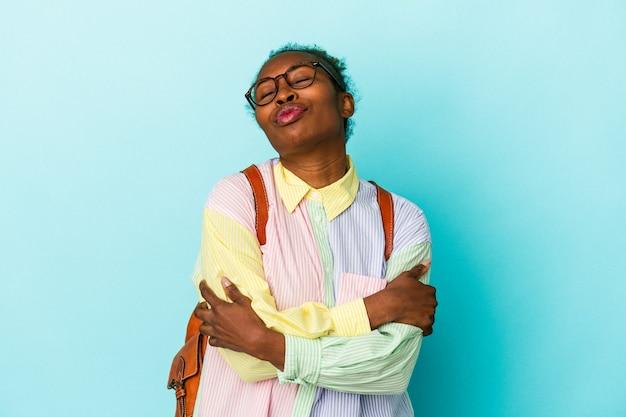 孤立した背景の抱擁、のんきと幸せな笑顔の若い学生アフリカ系アメリカ人女性。
