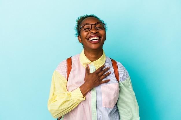 孤立した背景の上の若い学生アフリカ系アメリカ人の女性は、胸に手を置いて大声で笑います。