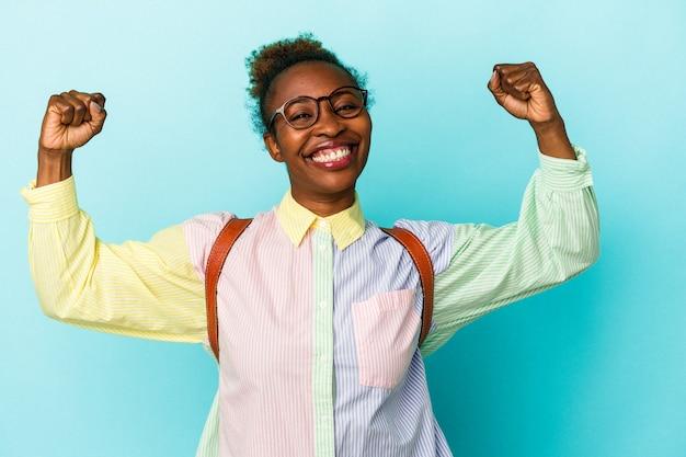 女性の力の象徴である腕で強さのジェスチャーを示す孤立した背景上の若い学生アフリカ系アメリカ人女性