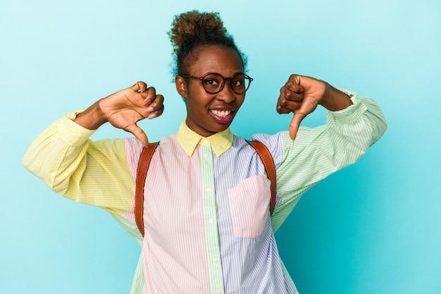 親指を下に示し、嫌悪感を表現する孤立した背景上の若い学生アフリカ系アメリカ人女性。