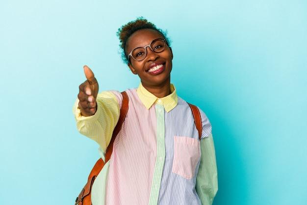 挨拶のジェスチャーでカメラに手を伸ばす孤立した背景上の若い学生アフリカ系アメリカ人女性。