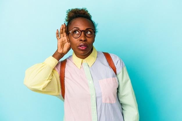 ゴシップを聴こうとしている孤立した背景上の若い学生アフリカ系アメリカ人女性。