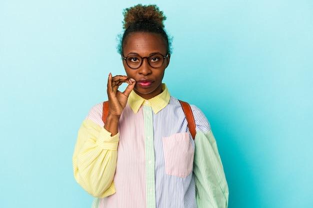 秘密を保持している唇に指で孤立した背景上の若い学生アフリカ系アメリカ人女性。