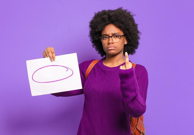 Молодая студентка афро-женщина чувствует себя сердитой, раздраженной, мятежной и агрессивной, переворачивает средний палец, сопротивляется