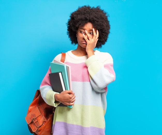 退屈で、退屈で退屈な仕事をした後、退屈で欲求不満で眠い感じの若い学生アフロ女性