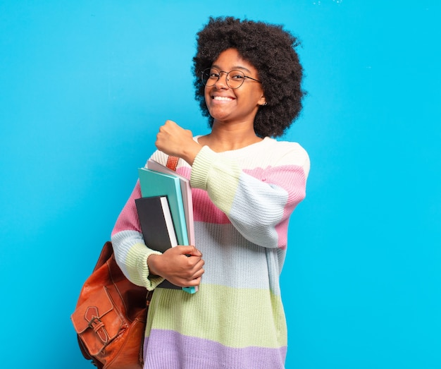若い学生のアフロ女性は、挑戦に直面したり、良い結果を祝ったりするときに、幸せで、前向きで、成功し、やる気を出す