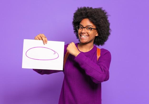 若い学生のアフロ女性は、挑戦に直面したり、良い結果を祝ったりするときに、幸せで、前向きで、成功し、やる気を感じます