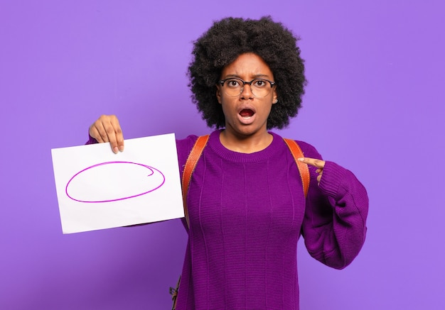Young student afro woman feeling happy, surprised and proud, pointing to self with an excited, amazed look