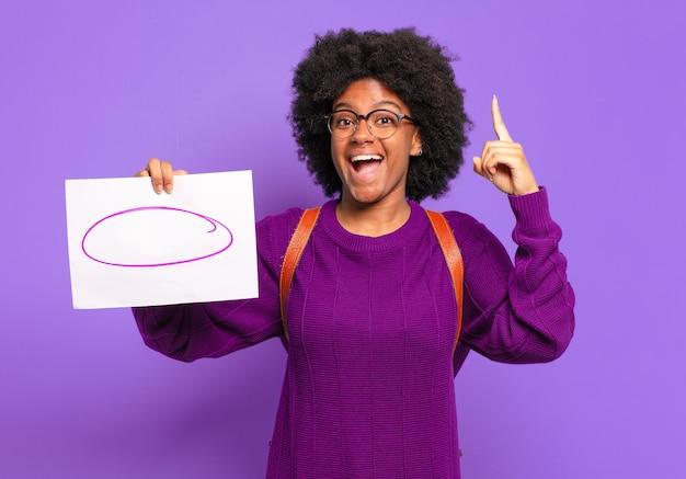 Молодая студентка-афро-женщина почувствовала себя счастливой и взволнованной гением, реализовав идею, весело подняв палец, эврика!