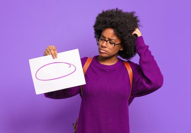 Молодой студент афро-женщина чувствует себя озадаченным и сбитым с толку, почесывая голову и глядя в сторону