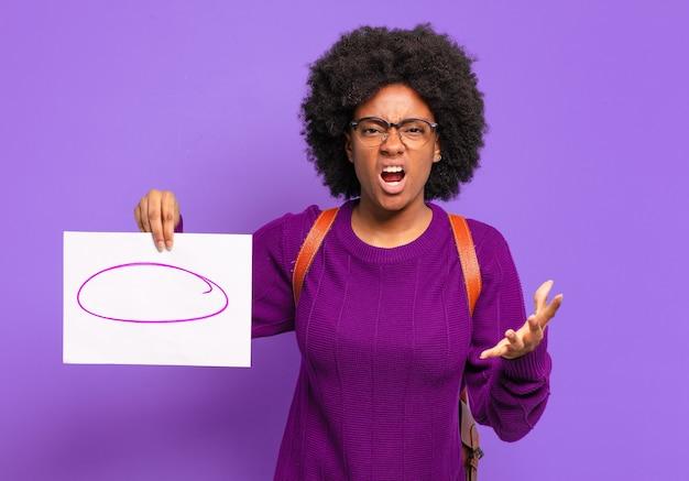 怒っている、イライラしている、欲求不満の叫び声のwtfまたはあなたの何が悪いのかを探している若い学生のアフロ女性