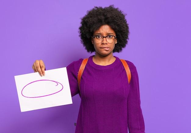 Молодая студентка-афро-женщина выглядит озадаченной и сбитой с толку, нервно прикусывает губу, не зная ответа на проблему