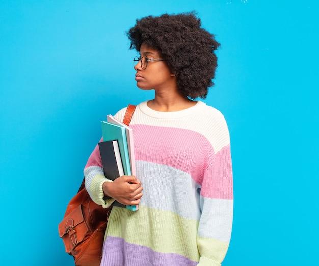 Молодая студентка афро-женщина на виде профиля, желающая скопировать пространство впереди, думает, воображает или мечтает